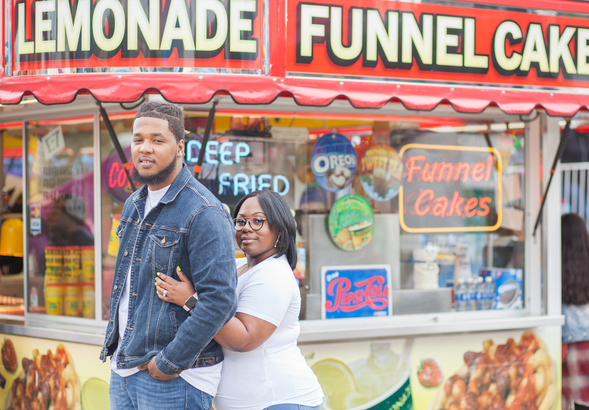 CARNIVAL PHOTO SHOOT DURHAM NORTH CAROLINA BRITTANY AND DEON IN FRONT OF CARNIVAL FOOD BOOTH