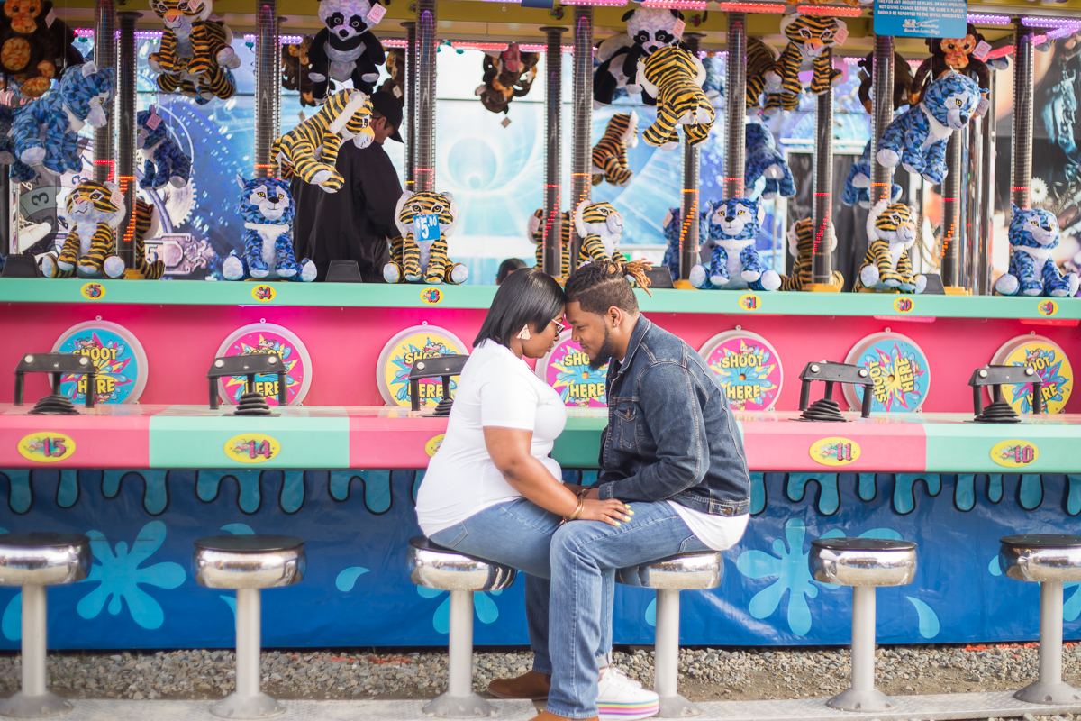 CARNIVAL PHOTO SESSION DURHAM NORTH CAROLINA BRITTANY AND DEON SITTING ON STOOLS IN FRONT OF GAME, THEIR FOREHEADS TOGETHER