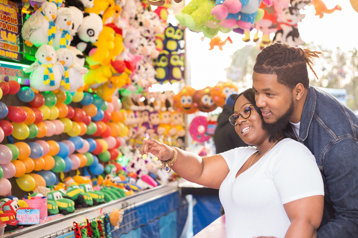 CARNIVAL PHOTO SESSION DURHAM NORTH CAROLINA DEON STANDING BEHIND BRITTANY, BRITTANY POINTING SOMETHING OUT AT BALLOON POPPING GAME