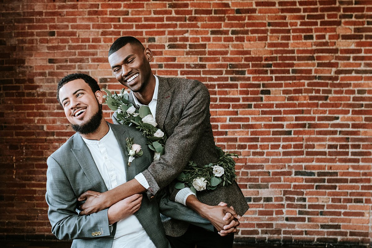 baltimore photo shoot candid of grooms laughing and holding hands