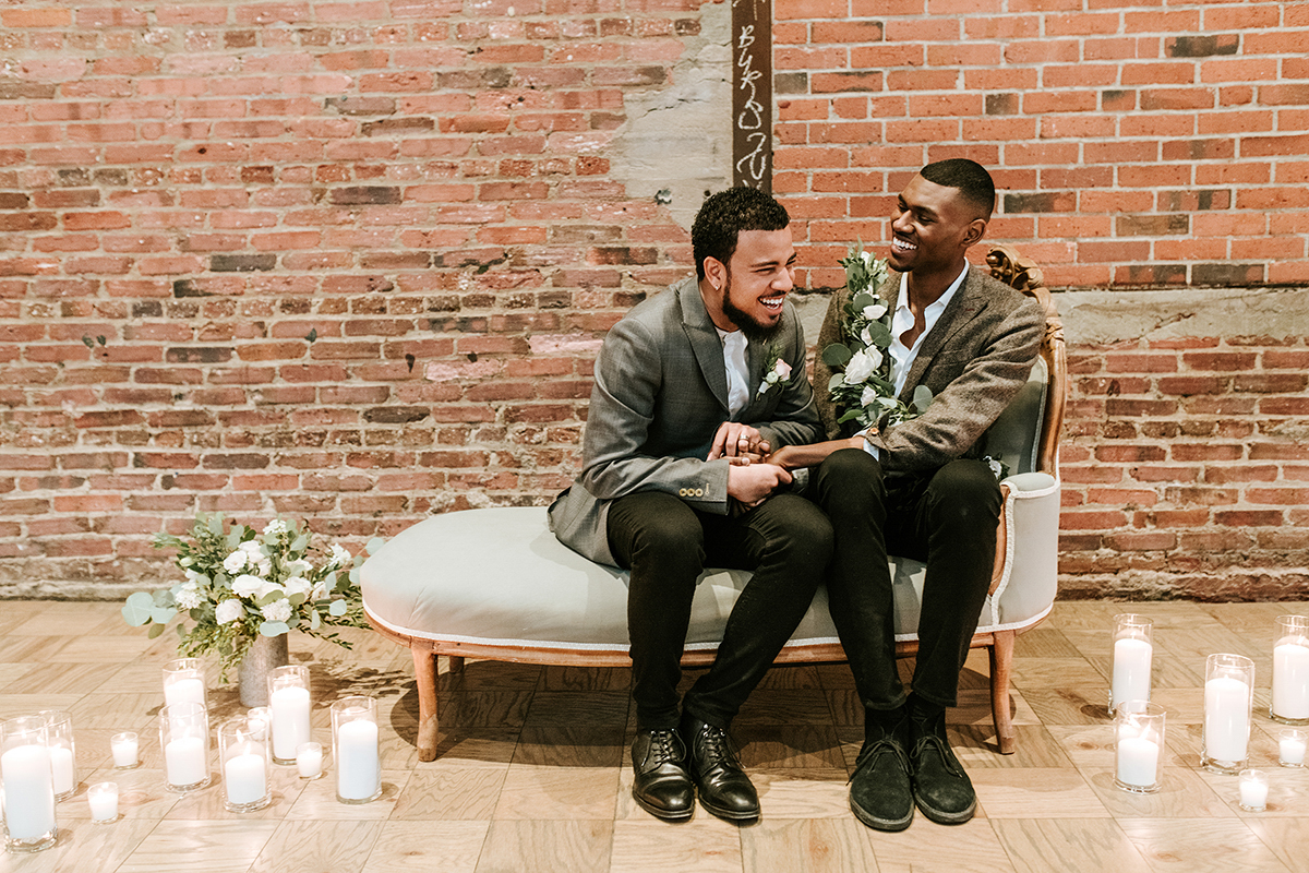baltimore photo shoot couple laughing on sofa and holding hands