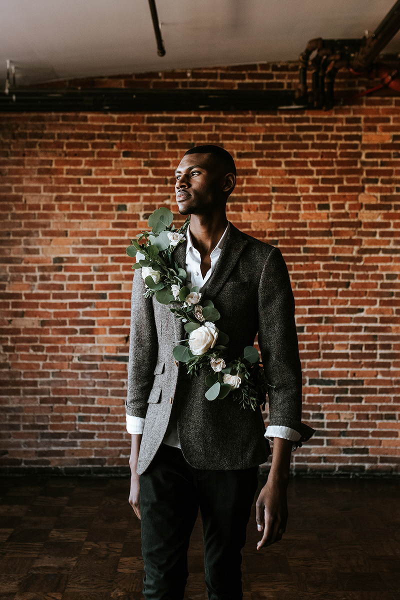 baltimore photo shoot portrait shot of hassan wearing floral sash looking off into distance, brick wall in background