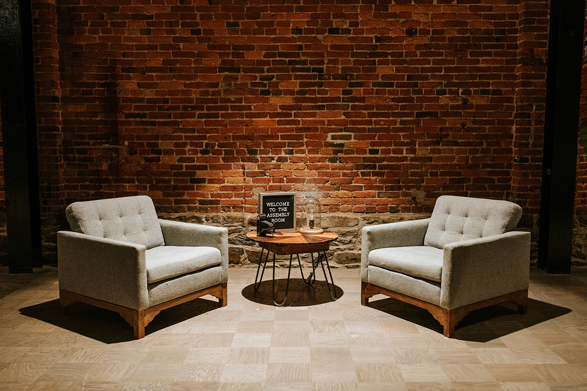 "baltimore photo shoot armchairs and end table with vintage camera and light; small sign on table reads ""welcome to the assembly room"""