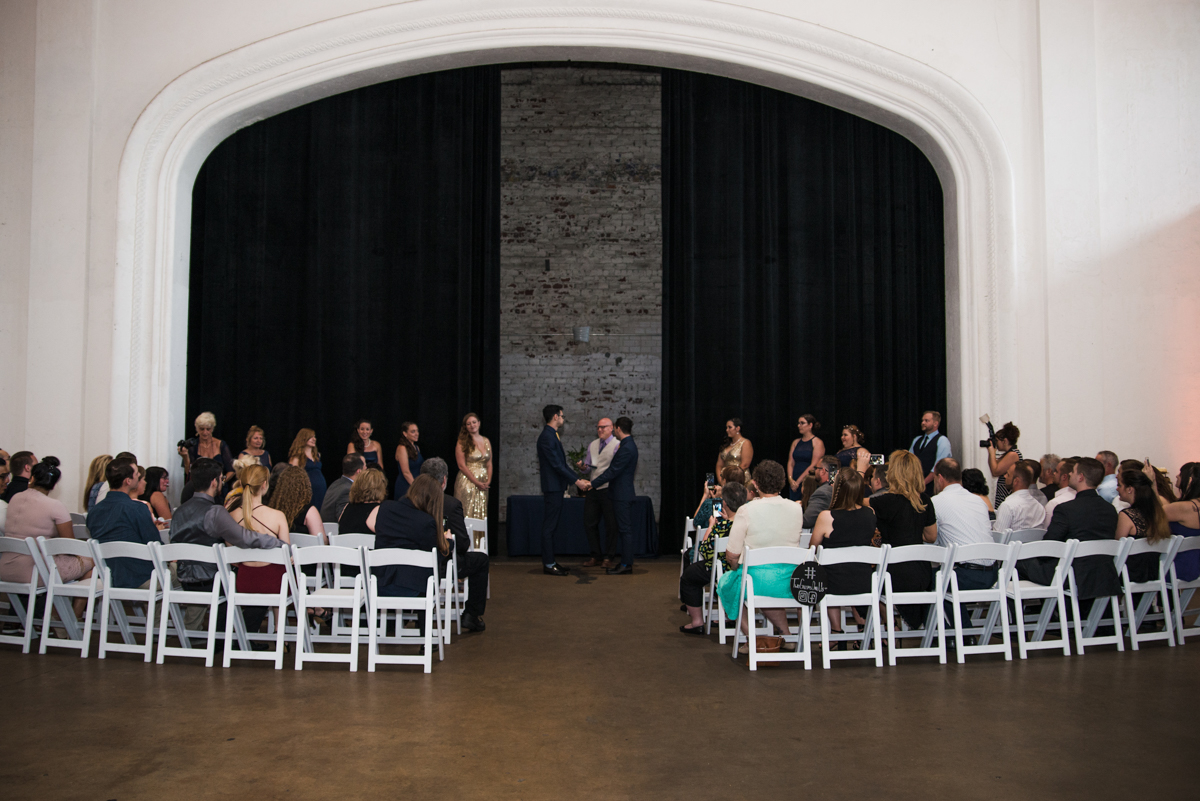 rialto theatre wedding ceremony in front of theatre curtains