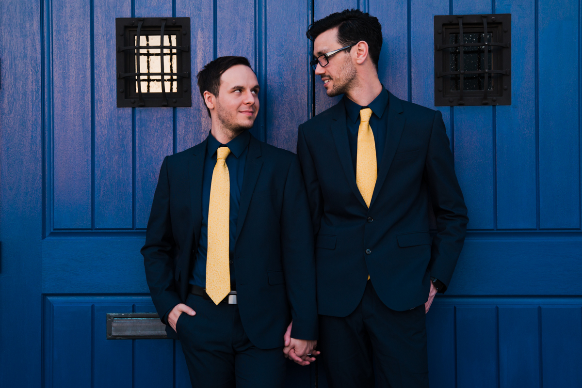 rialto theatre wedding couple holding hands staring at one another in front of brightly painted doors