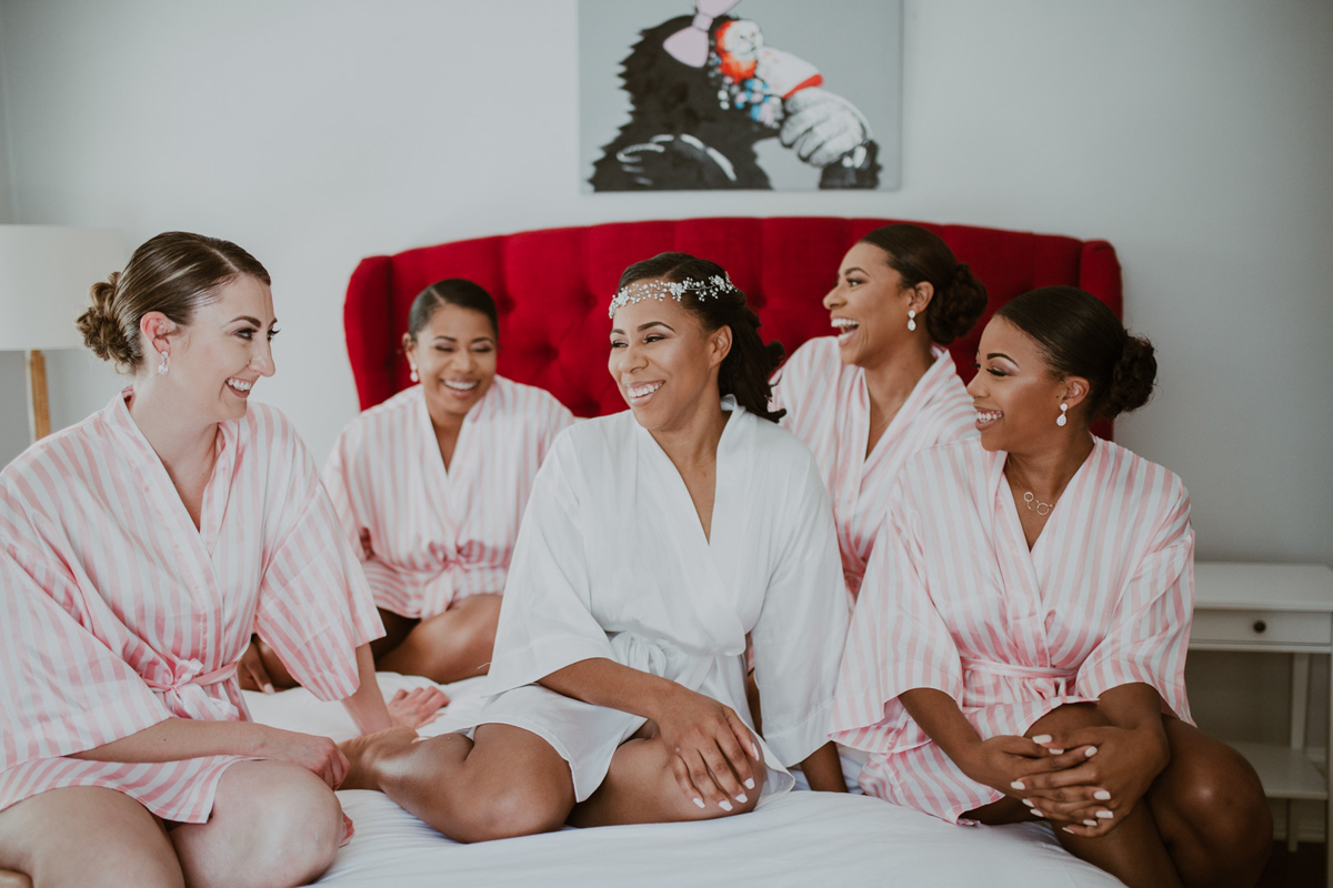 art-inspired levine museum wedding shavonne on bed laughing with bridesmaids