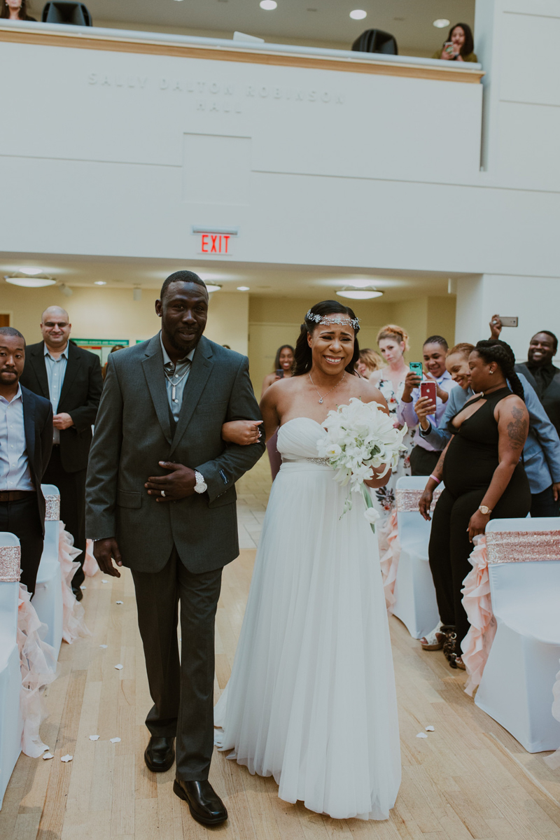 art-inspired levine museum wedding shavonne and father walking down aisle, shavonne emotional and excited guests in background