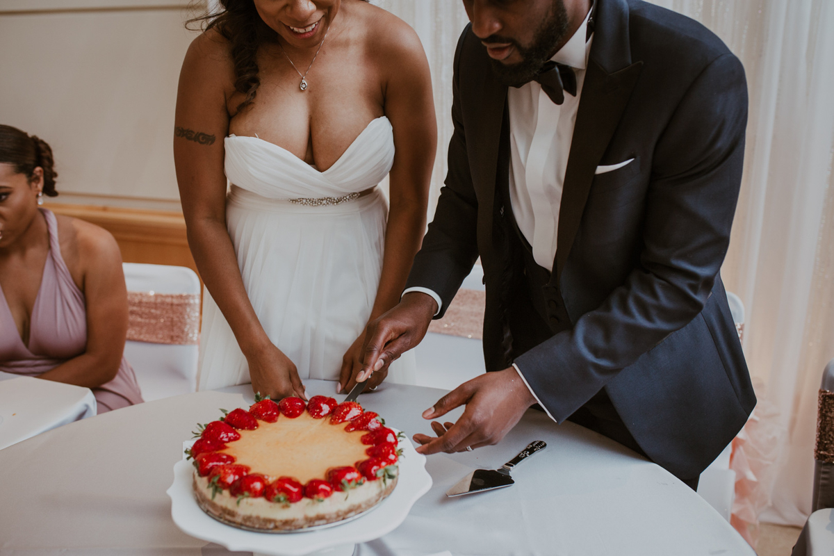 art-inspired levine museum wedding couple cutting cake topped with strawberries