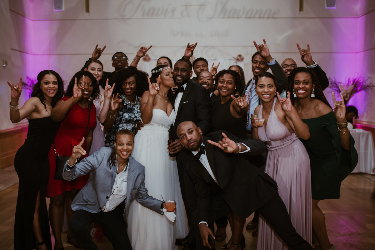 art-inspired levine museum wedding couple and guests together making longhorn hand gesture