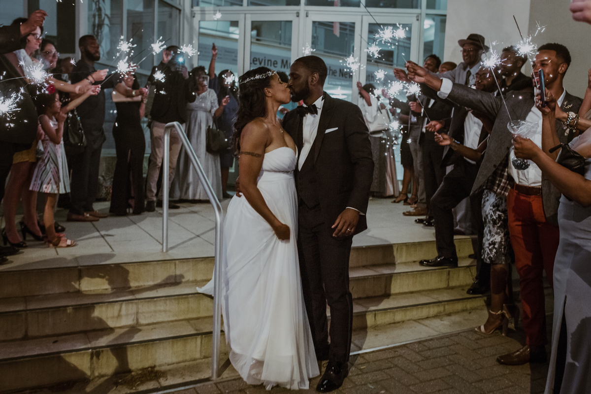 art-inspired levine museum wedding kiss outside museum while guests surround them with sparklers