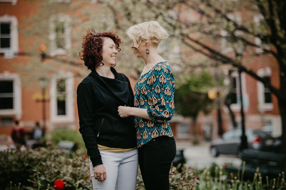BALTIMORE COFFEE SHOP ENGAGEMENT SESSION COUPLE IN GARDEN LAUGHING CANDID
