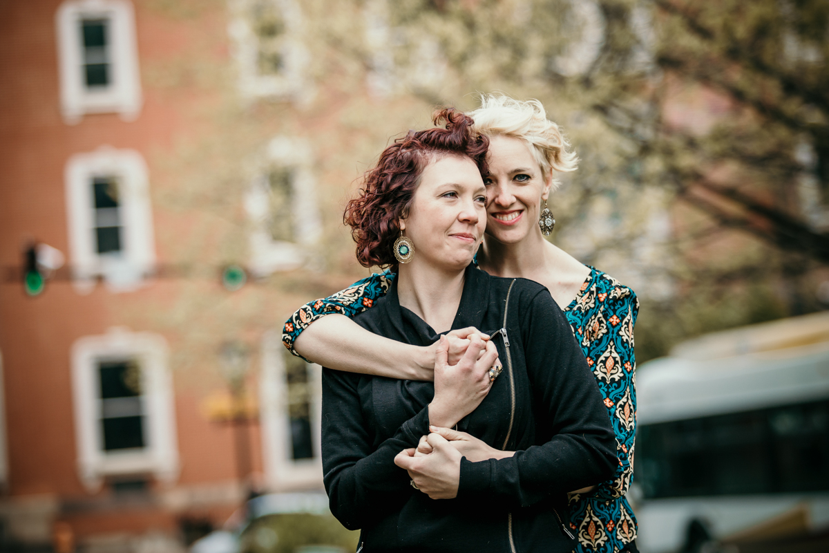 BALTIMORE COFFEE SHOP ENGAGEMENT SESSION EMBRACE IN GARDEN, BREEZE BLOWING LIZ AND ALI'S HAIR