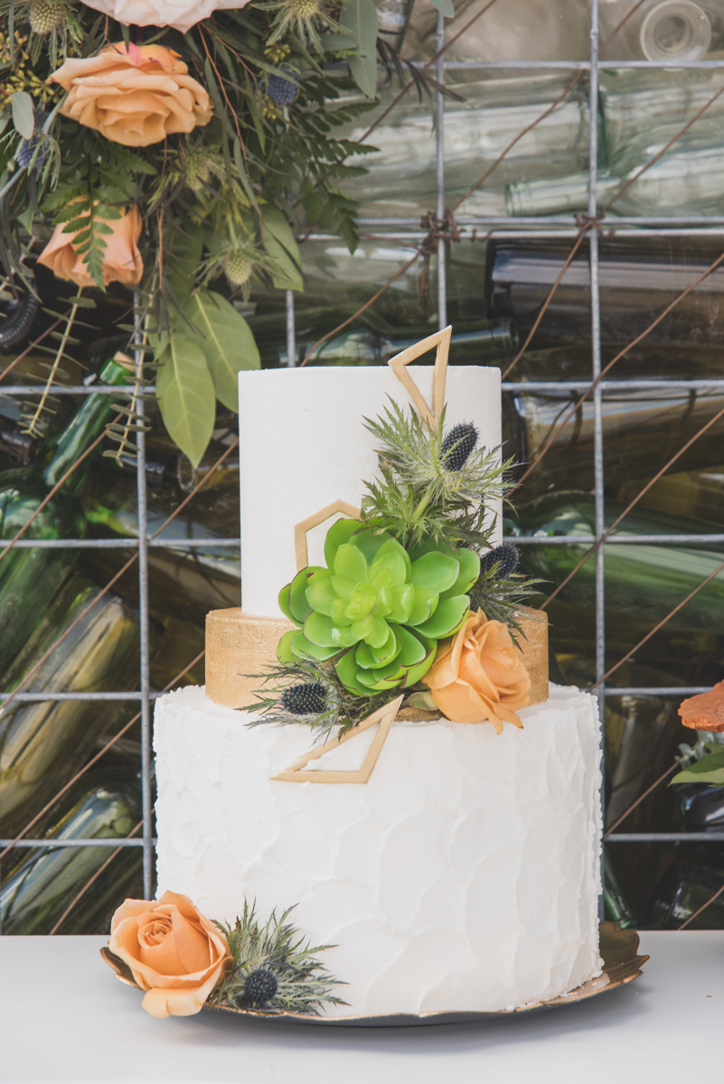 multi-cultural desert elopement cake decorated wiht geometric gold shapes, roses, and succulents