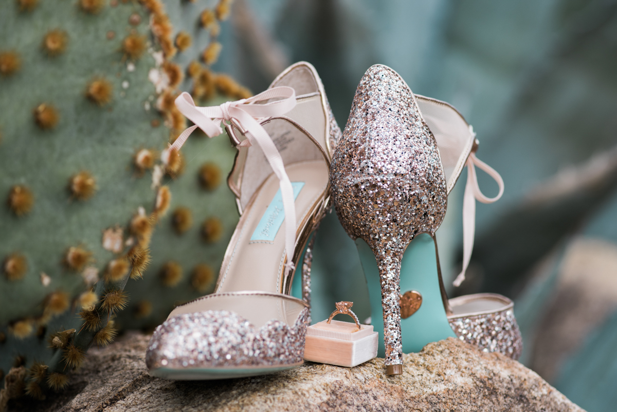 multi-cultural desert elopement heels and ring on rock near a cactus