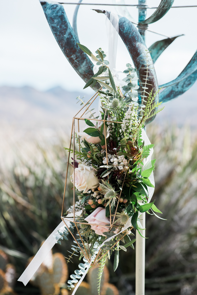 multi-cultural desert elopement geometric terranium with flower arrangement