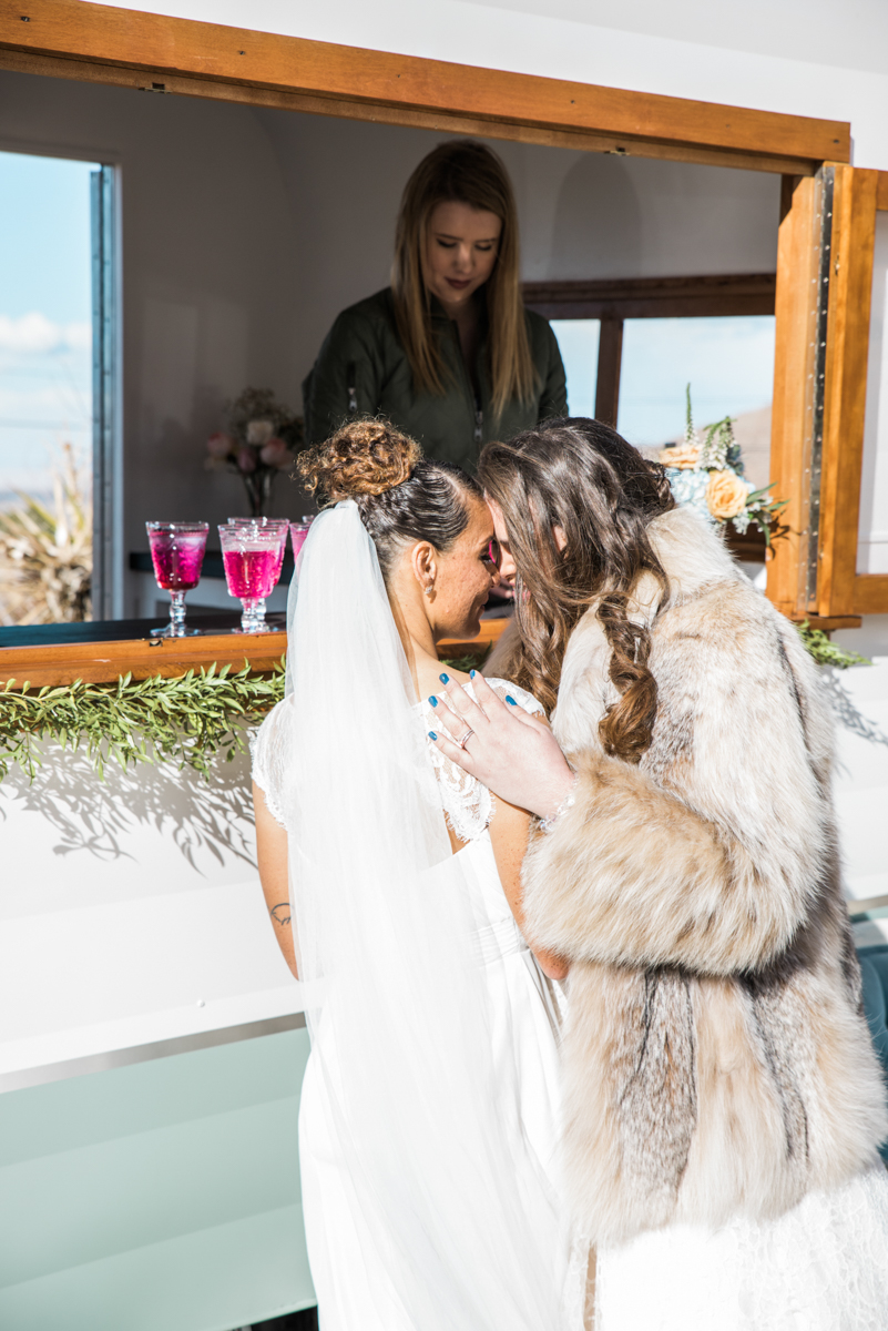 multi-cultural desert elopement brides embrace in front of bar