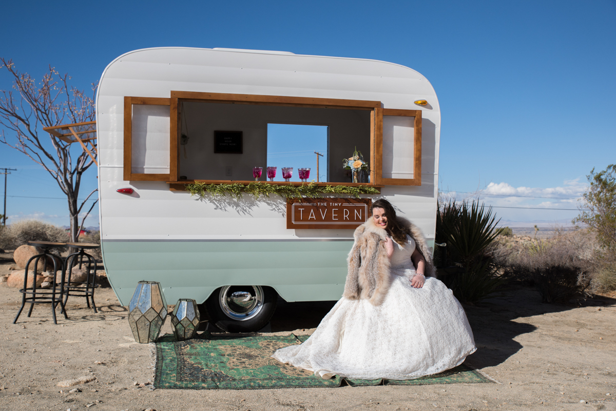 multi-cultural desert elopement bride sitting in front of trailer where drinks are served