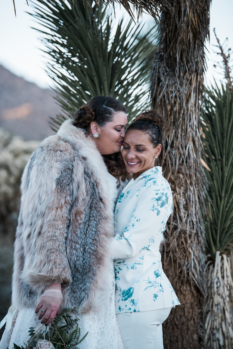 multi-cultural desert elopement kiss on forehead by tree