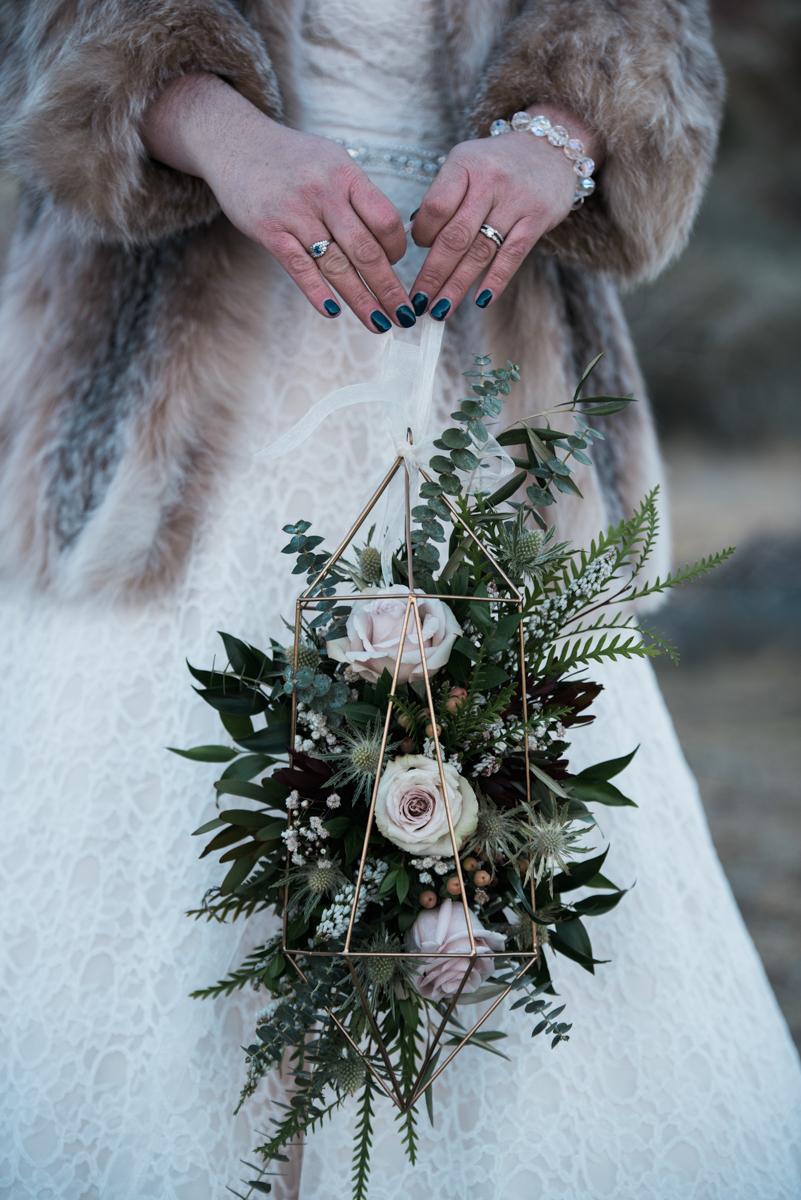 multi-cultural desert elopement bride holding terranium