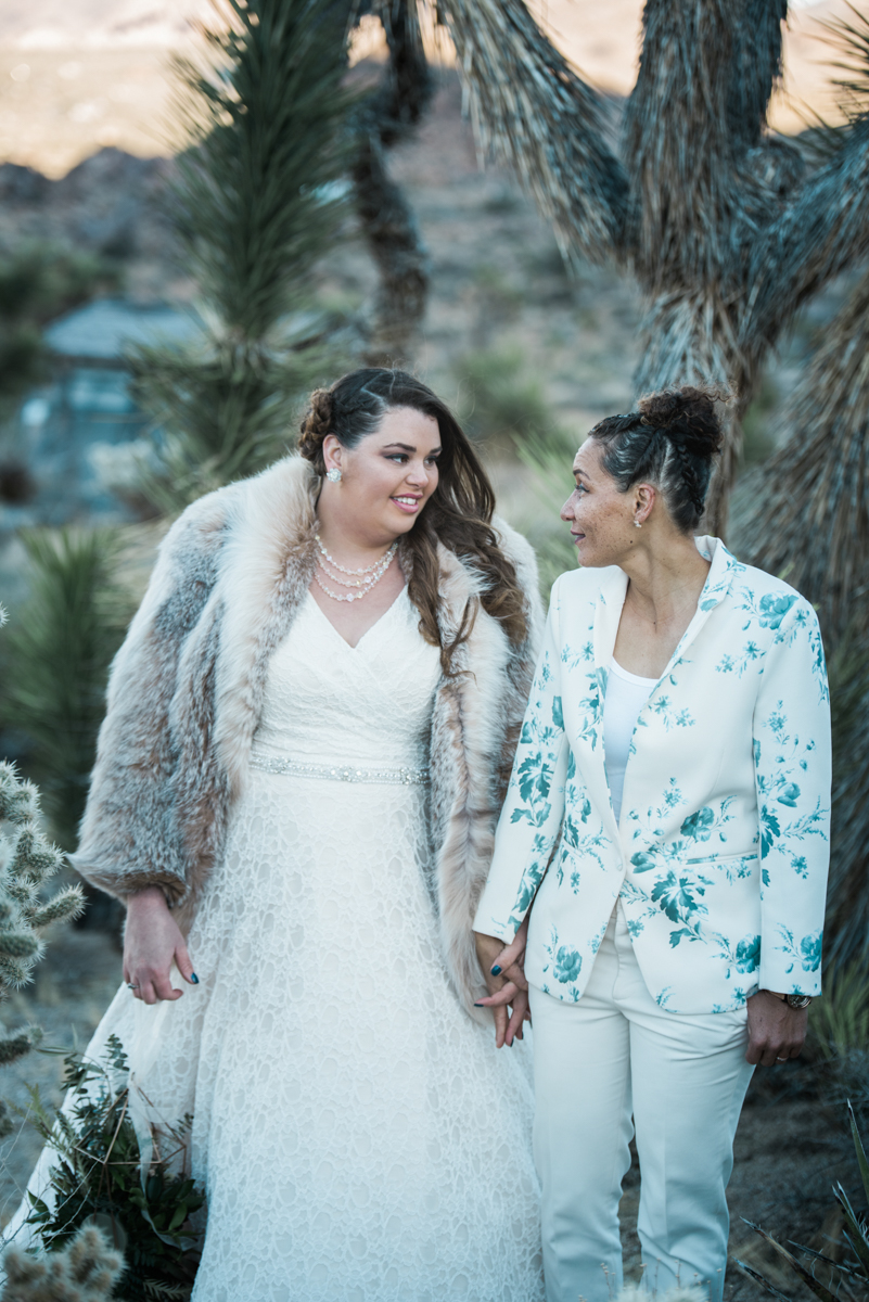 multi-cultural desert elopement brides holding hands looking at each other