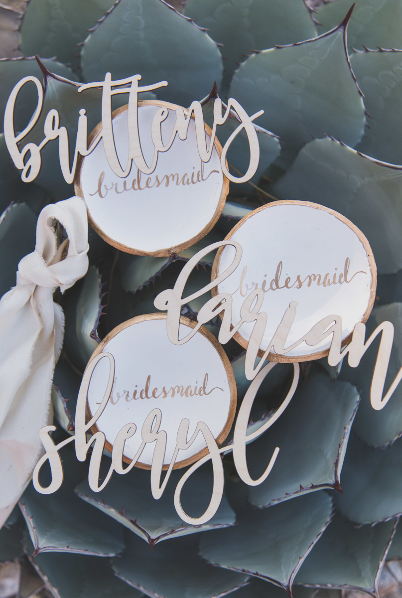 """multi-cultural desert elopement circle plates with """"bridesmaid"""" written on it and cutouts of bridesmaids' names"""