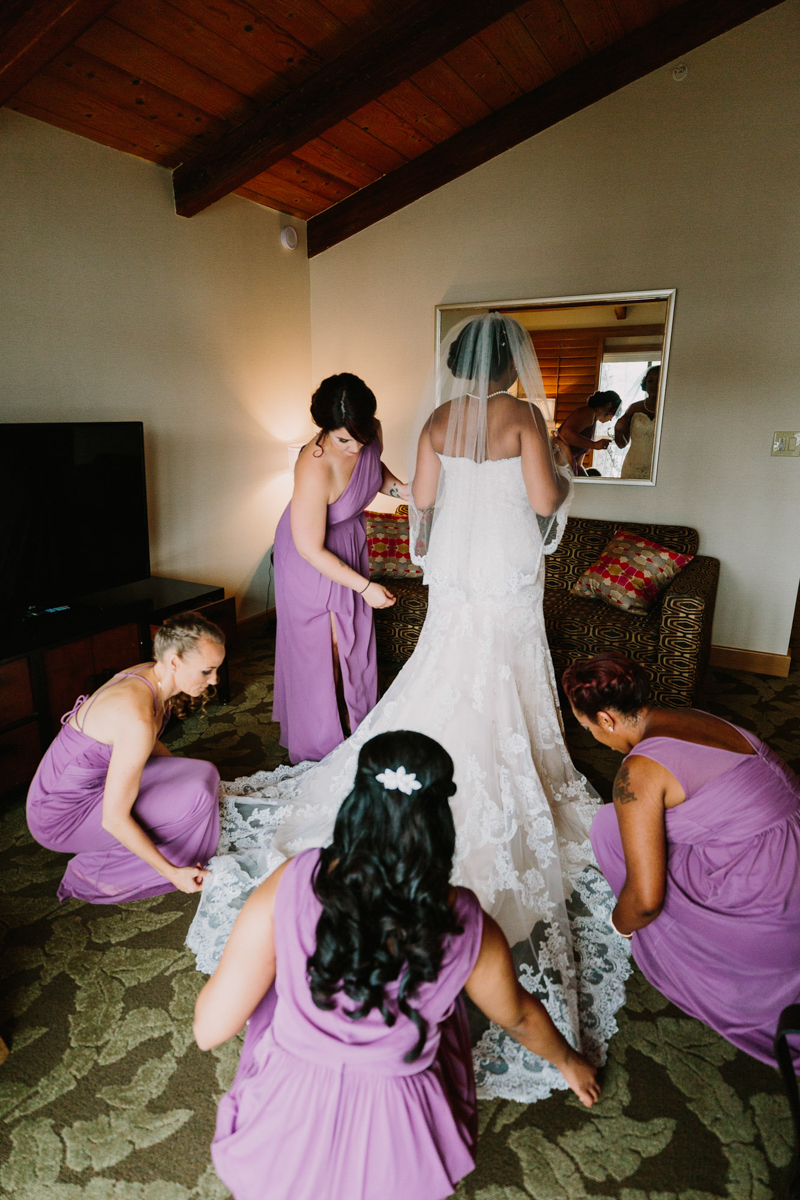 San Diego Tropical-Inspired Wedding bridesmaids adjusting bride's dress