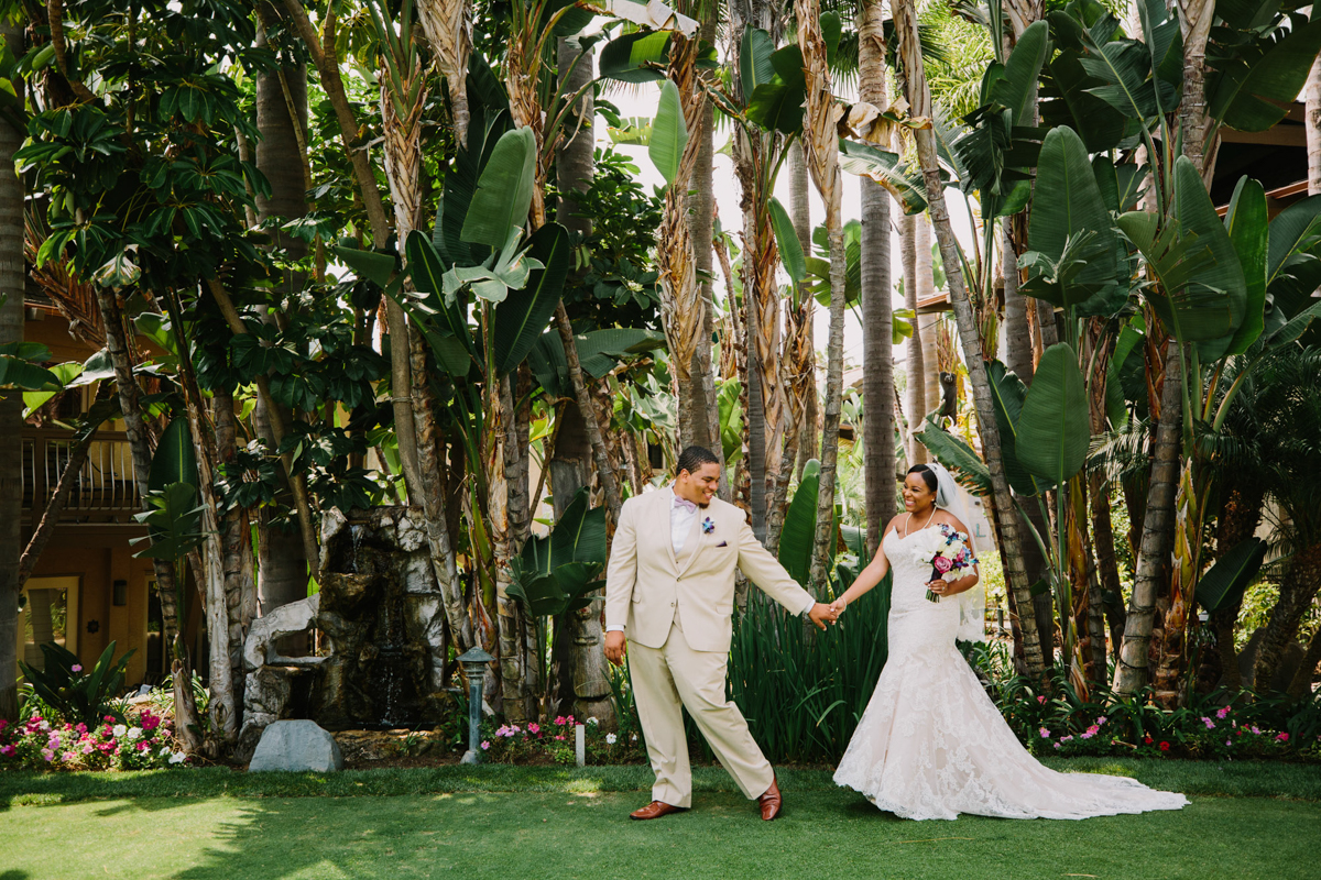 San Diego Tropical-Inspired Wedding william leading janelle by the hand in garden, palm trees in background