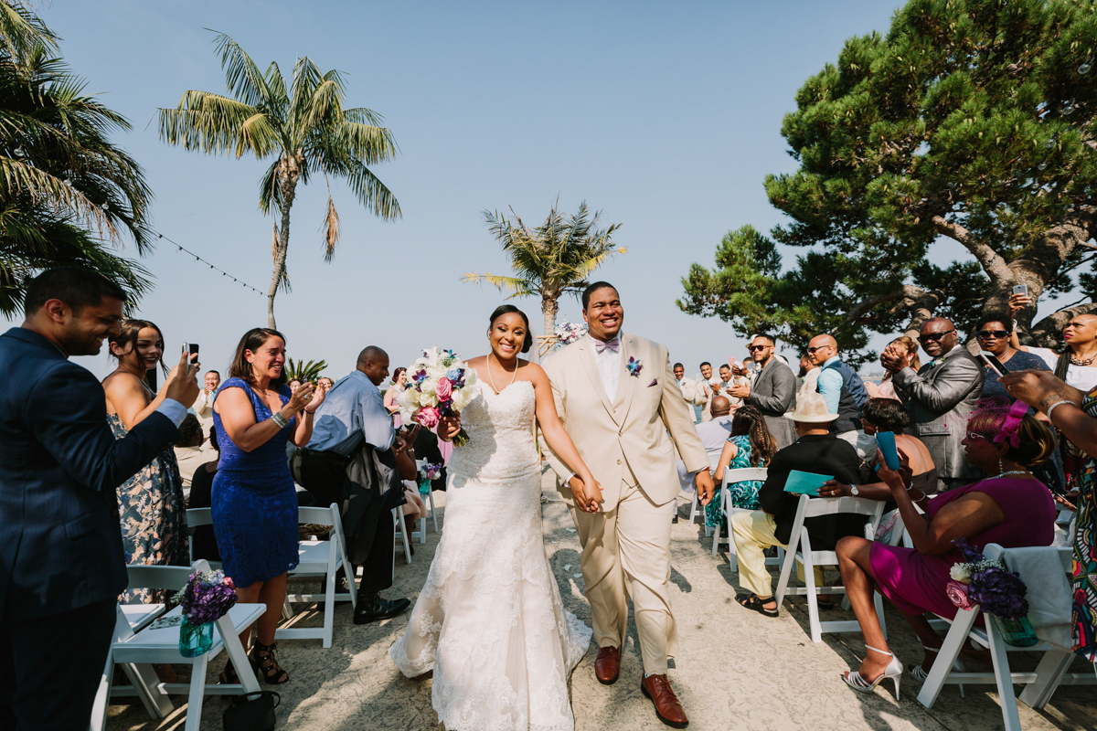 San Diego Tropical-Inspired Wedding newly married couple walking up aisle hand in hand as guests clap