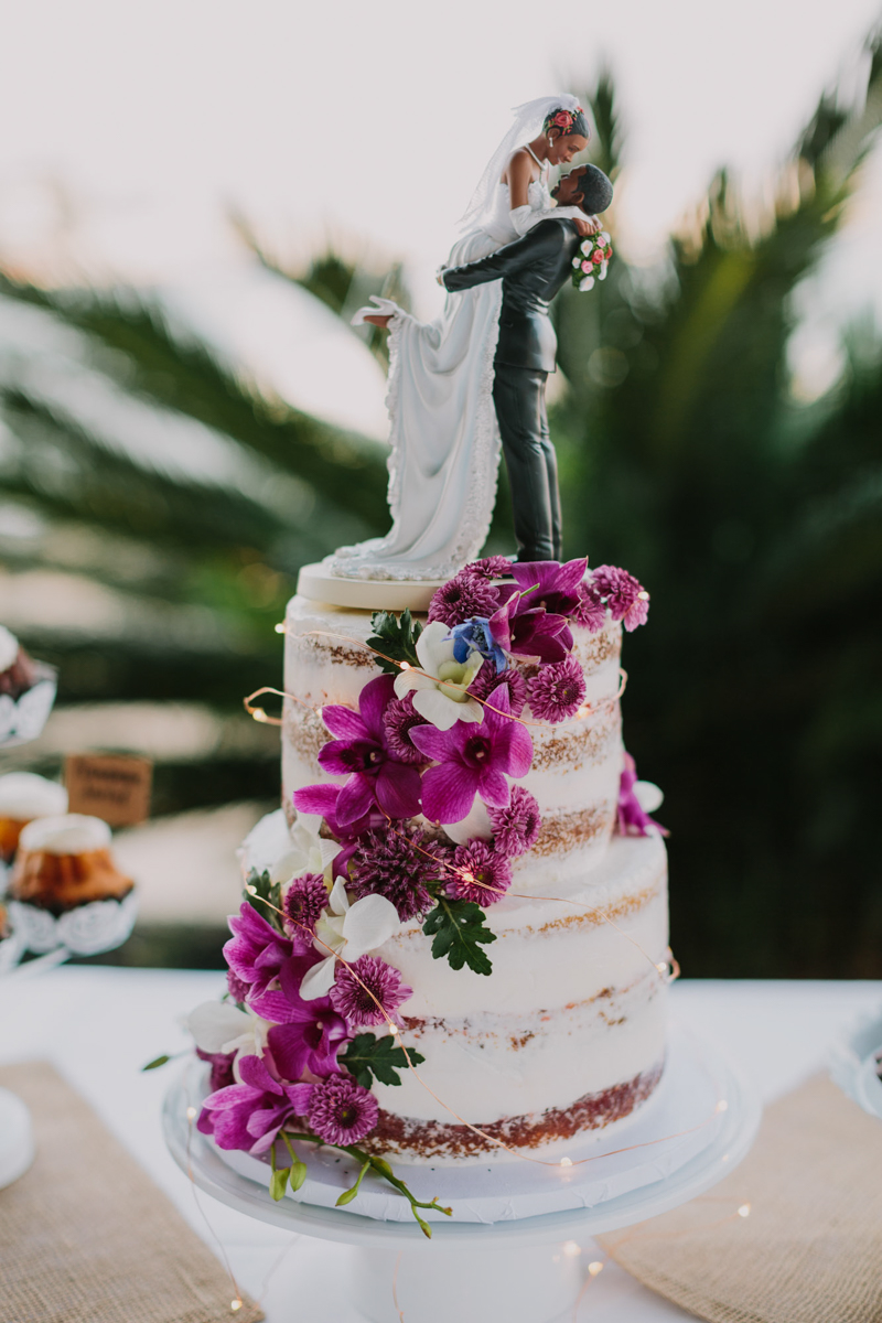 San Diego Tropical-Inspired Wedding wedding cake adorned with flowers and cake topper of bride lifting groom