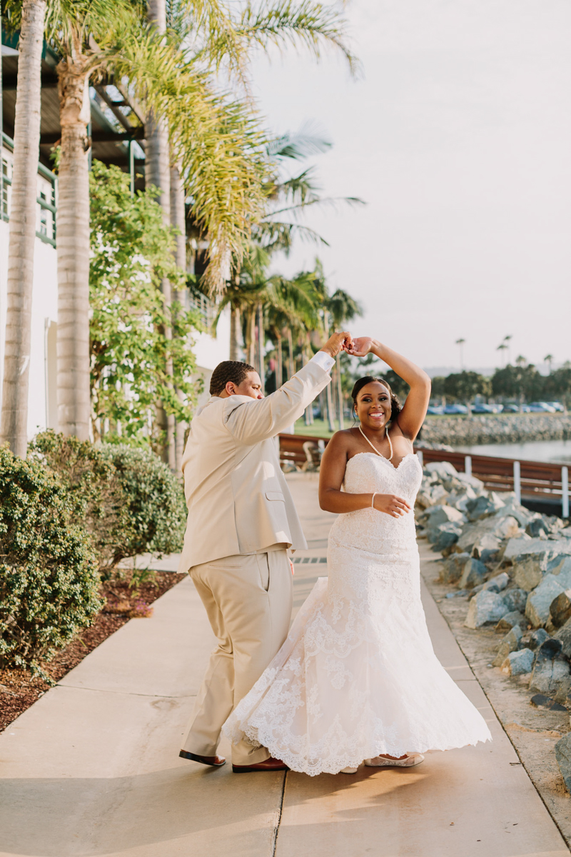 San Diego Tropical-Inspired Wedding william twirling janelle on outside path