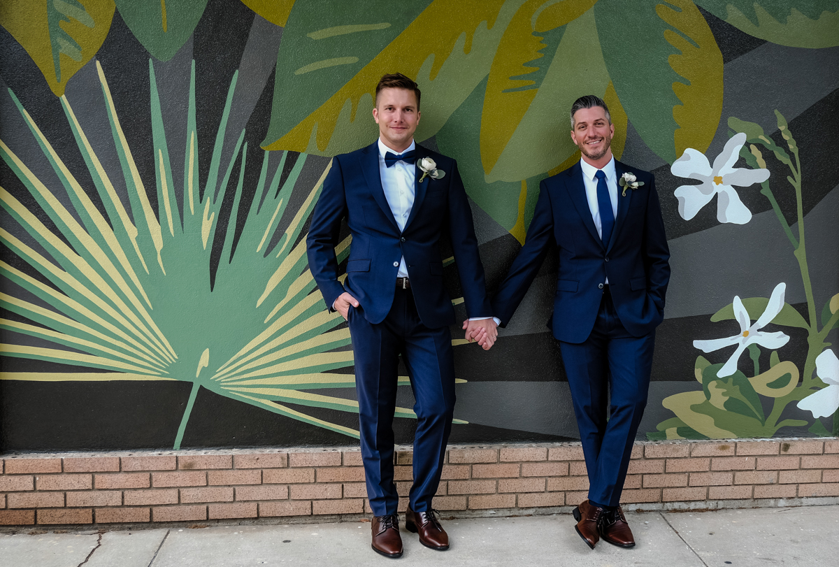 Classic southern style wedding savannah georgia couple holding hands in front of flora-themed mural