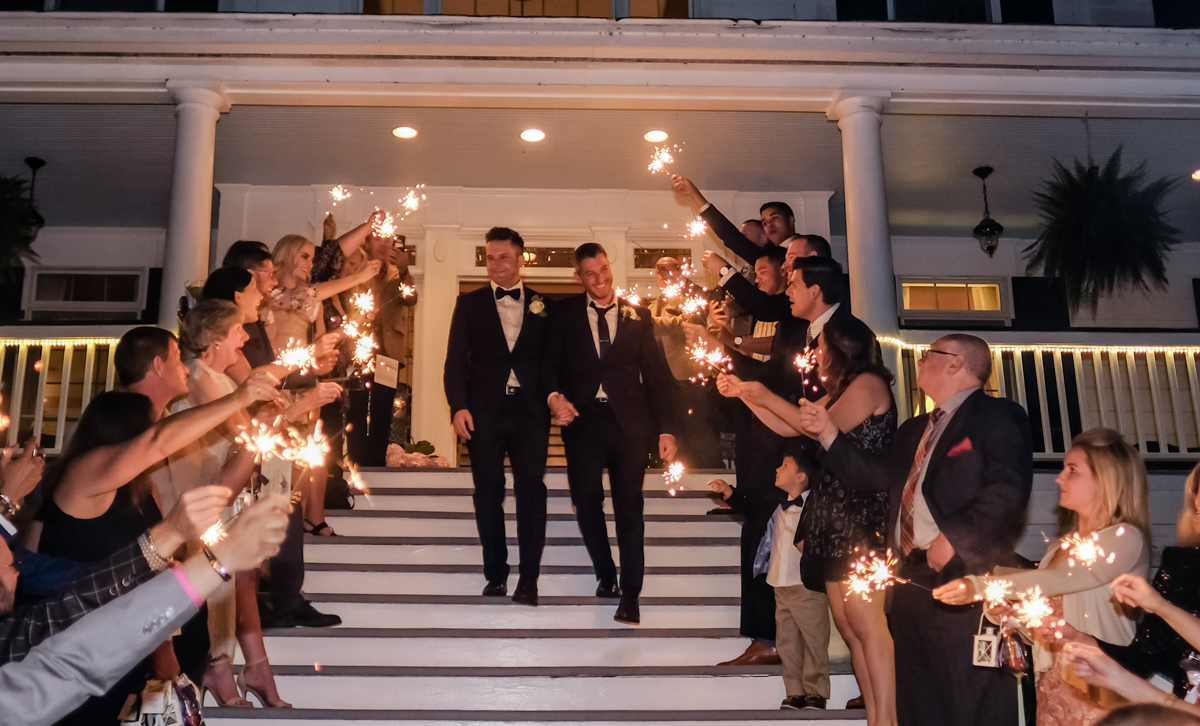 Classic southern style wedding savannah georgia grooms walking down porch steps with guests holding sparklers