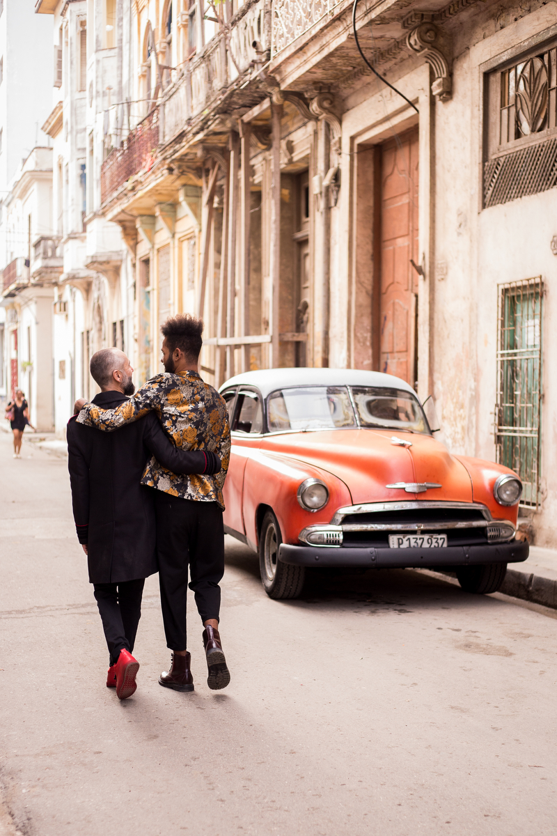 lovers in havana couple walking away with arms around each other, vintage car parked near