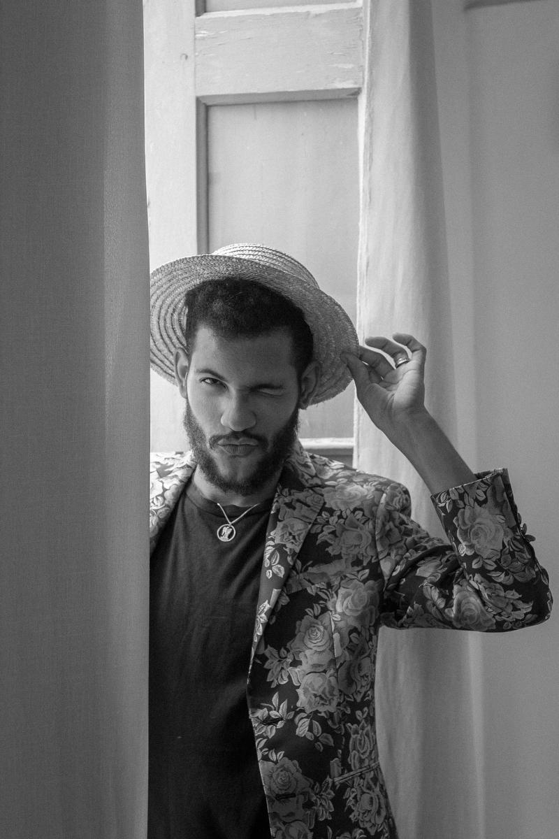 lovers in havana felix in doorway winking and modeling a new straw hat