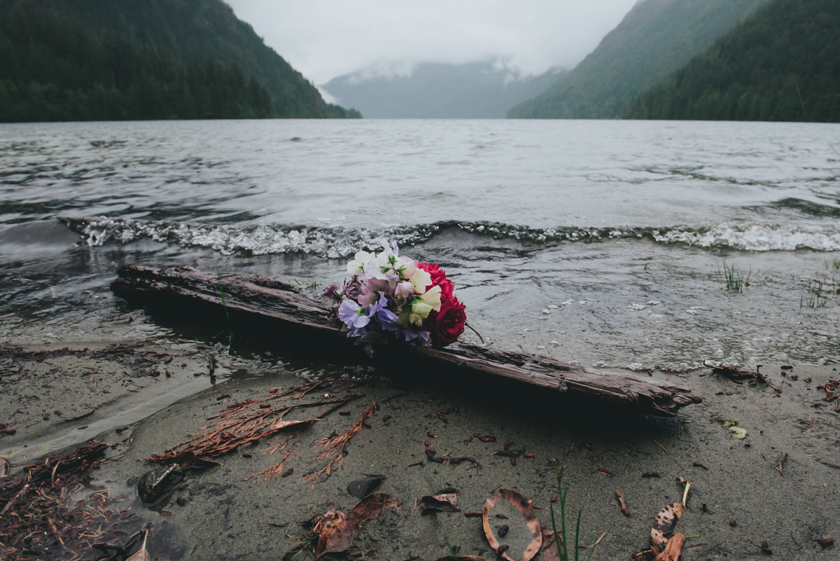 Cameron Lake Photo Session BC Canada bouquet resting on driftwood with wave rolling in from lake