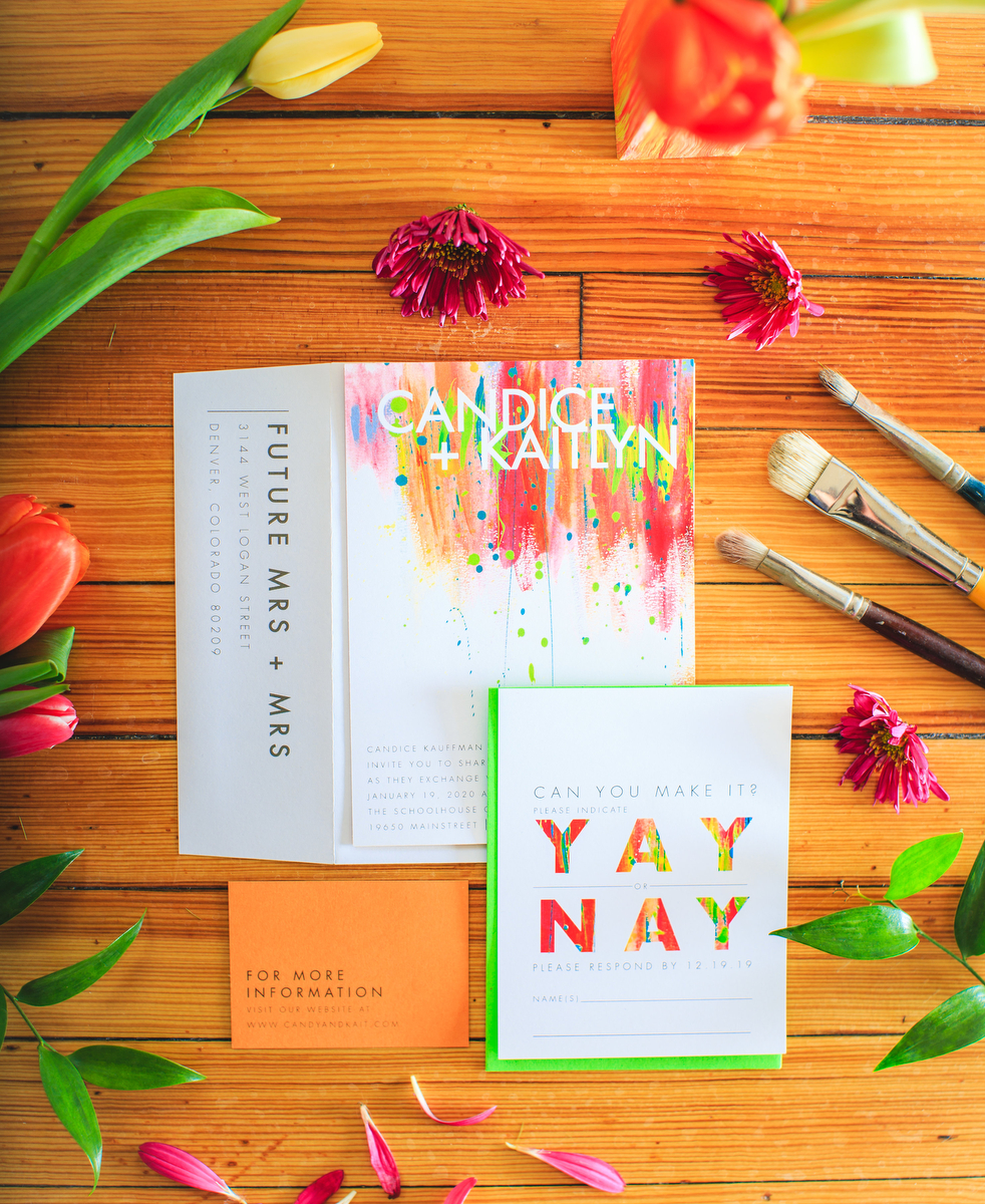 Love Out Loud Parker Colorado Styled Shoot invitation, custom envelope, and rsvp surrounded by flowers and paint brushes