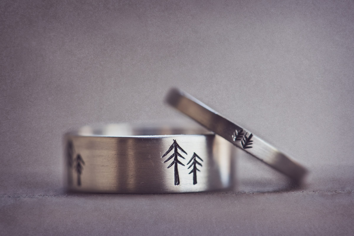 circle oak ranch farm wedding california grooms' wedding bands etched with minimalist pine tree designs