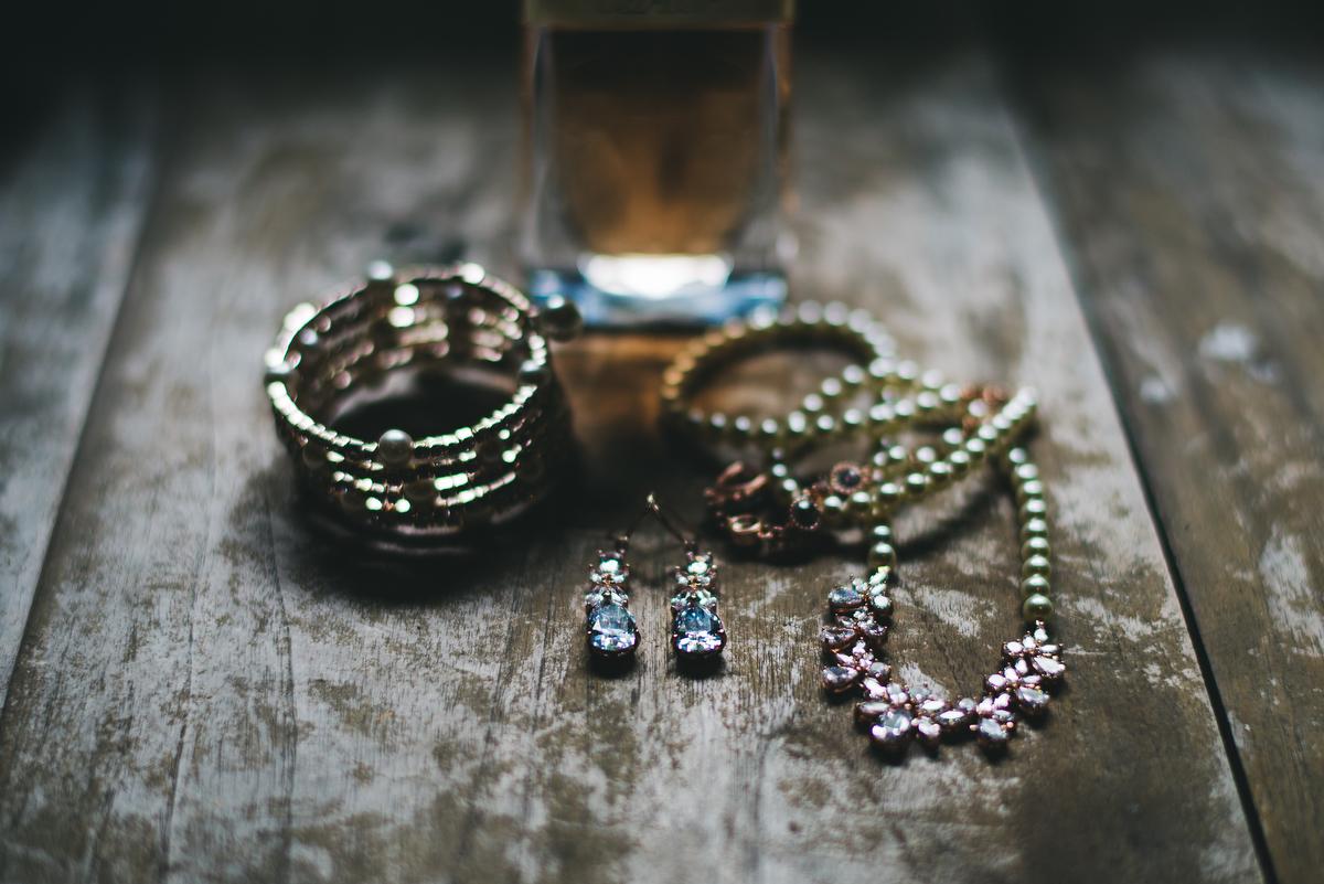 fairytale garden wedding vero beach florida jewelry and perfume on distressed wooden table
