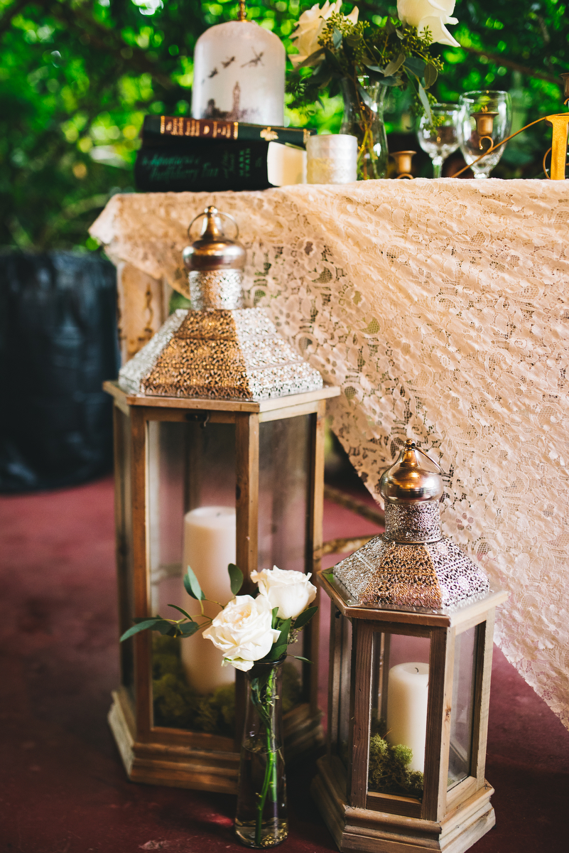 fairytale garden wedding vero beach florida lanterns with candles and small vase of roses on floor in front of main table