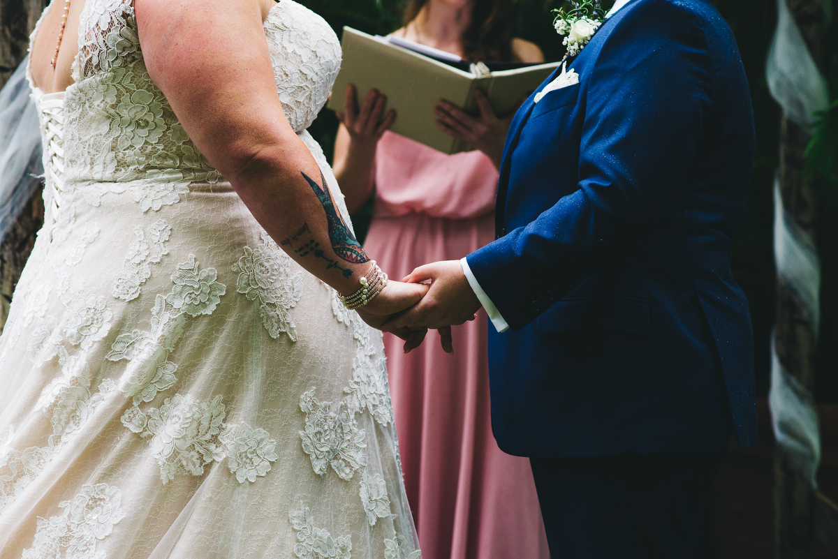 fairytale garden wedding vero beach florida stephanie and samantha holding hands during ceremony