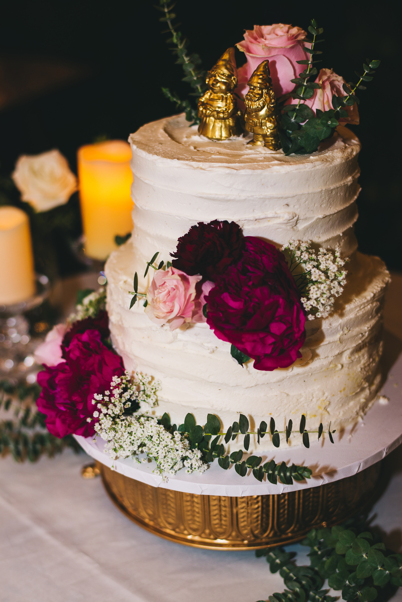 fairytale garden wedding vero beach florida wedding cake decorated with flowers and golden gnomes as cake toppers