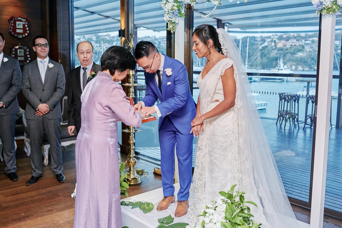 sri lankan, chinese, and harry potter wedding sydney australia ceremony daniel's mother handing him sari