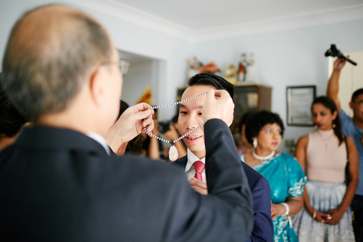 sri lankan, chinese, and harry potter wedding sydney australia daniel;s father putting necklace on daniel