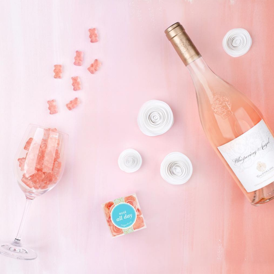 10 stylish gifts to give your wedding party sugarfina rose all day rose-flavored gummy bears in package, in wine glass beside bottle of rose and paper flowers