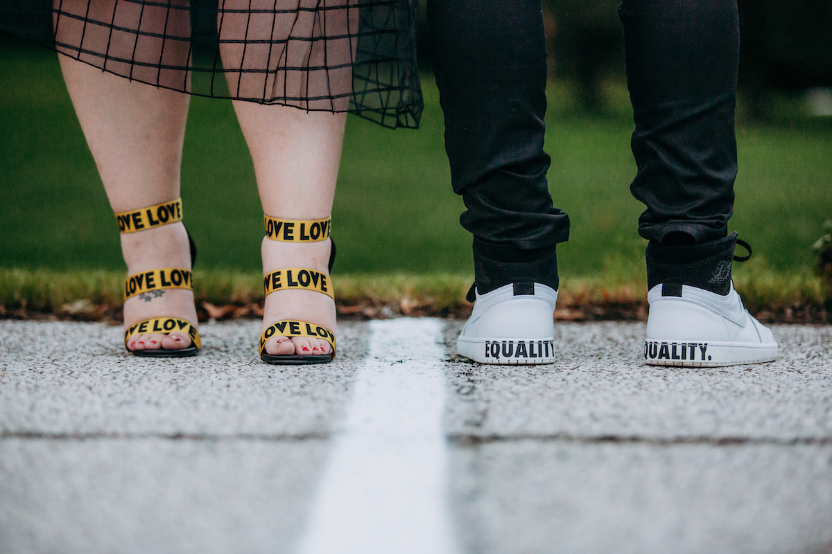 """engagement photo shoot at akron art museum alysse's heels reading """"love'"""" and backs of gio's sneakers reading """"equality."""""""