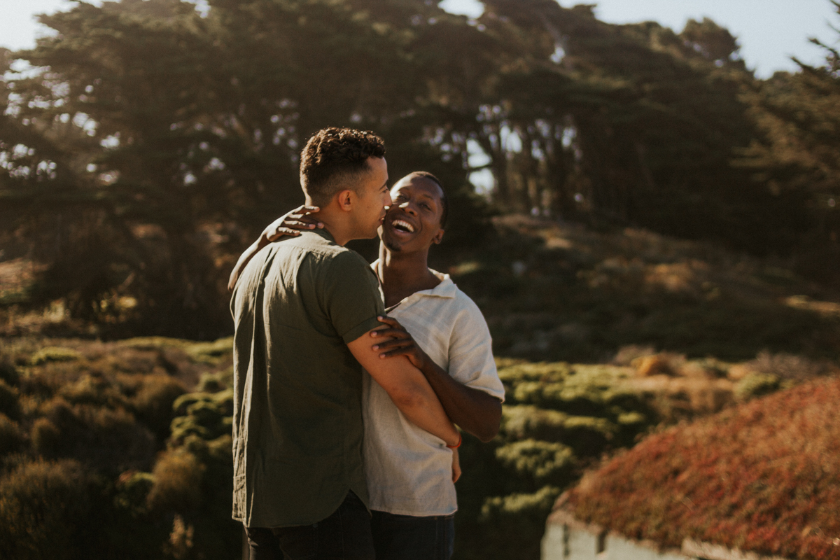 couples session baker beach san francisco california candid of couple laughing and embracing
