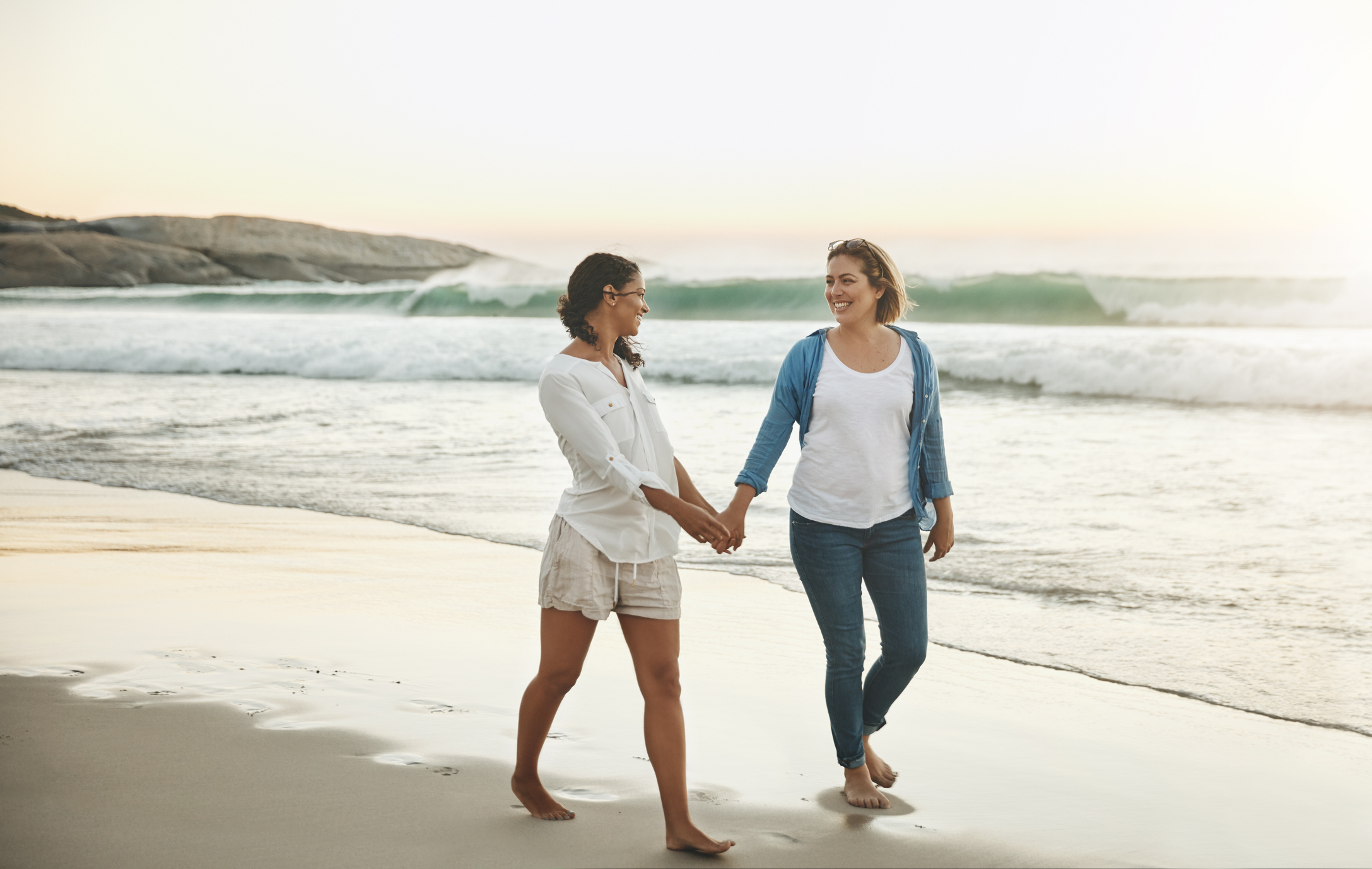 two women same-sex LGBTQ engaged couple walking on beach holding hands