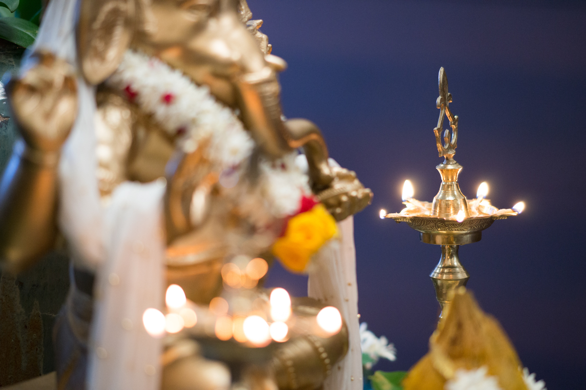 sri lankan wedding in sydney australia candles lit on candle holder and gold statue