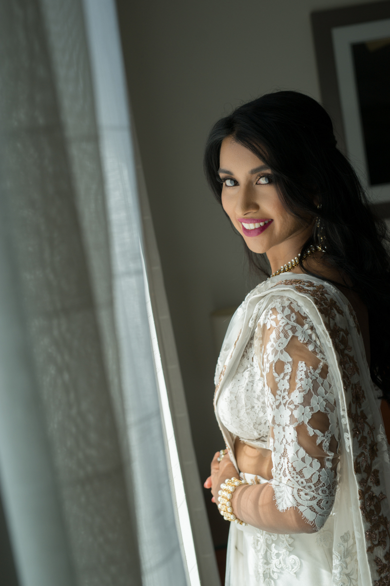 sri lankan wedding in sydney australia bride posing for camera in wedding outfit by window