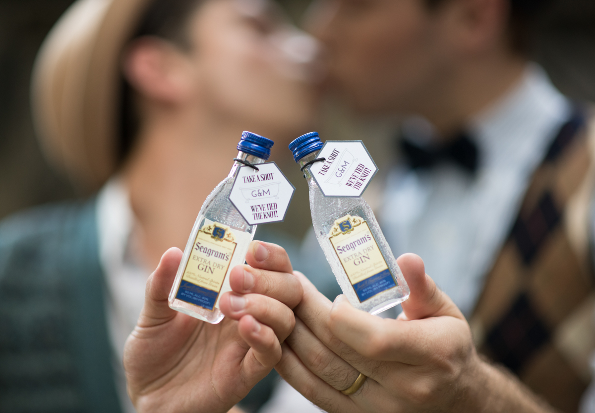 "vintage wedding editorial at the art factory paterson new jersey kiss while holding mini bottles of gin for guest favors; tags read ""take a shot, we've tied the knot!"""
